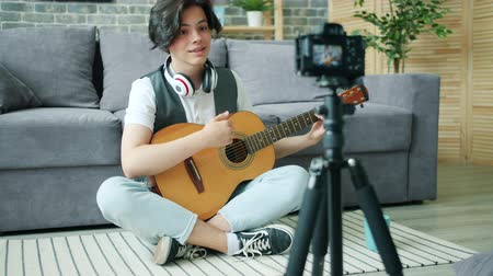 akusztikus : Teenage guitarist recording video for internet blog holding guitar sitting on floor at home looking at camera on tripod. Music, teenagers and hobby concept.