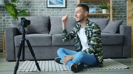 kciuk : Emotional vlogger recording video for vlog talking for camera in apartment gesturing showing thumbs-up smiling sitting on floor alone. People and occupation concept.