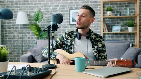 kytarista : Young man singer is playing the guitar and singing in microphone recording podcast in home studio. Blogging, musical instruments and lifestyle concept.