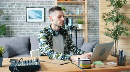 journalistiek : Handsome guy is using professional microphone and laptop talking recording podcart in apartment enjoying occupation. Bloggers and modern technology concept.