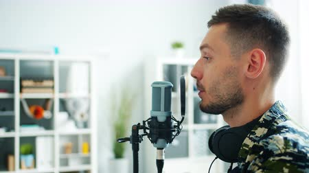 presentador : Close-up of male blogger attractive guy recording audio podcast for online blog talking in mic with expressive face. Mass media and modern people concept.