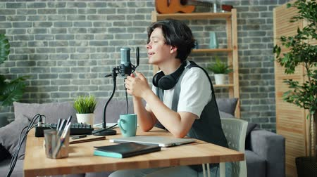 ゲスト : Good-looking teenager speaking in microphone in sound recording studio sitting at desk alone using modern equipment. Audio podcasts and adolescence concept. 動画素材