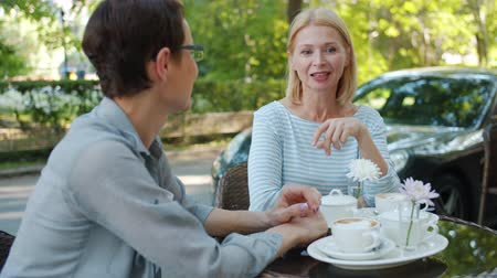 milestone : Beautiful mature woman is talking to female friend in street cafe smiling having fun enjoying warm summer day. Modern lifestyle, friendship and conversation concept.