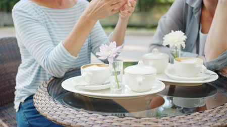 braccia aperte : Anonymous women in casual clothing are sitting at table in street cafe gesturing, focus on drinks cups of coffee and flowers. Lifestyle, lunch and summer concept. Filmati Stock