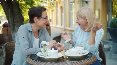 milestone : Slow motion of mature ladies in casual clothing socializing in outdoor cafe talking laughing enjoying warm summer day. Friendship and happiness concept. Stock Footage