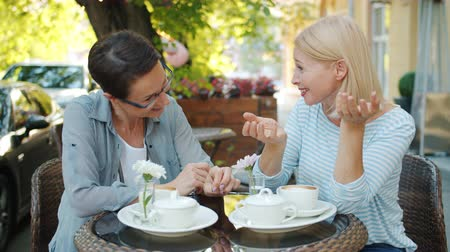 milestone : Cheerful adult women are laughing talking having fun relaxing in street cafe on summer day enjoying conversation and good company. People and joy concept. Stock Footage