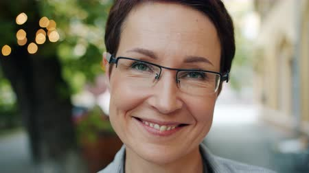 milestone : Close-up portrait of attractive mature businesswoman in glasses smiling looking at camera outdoors in city on summer day. People and urban background concept.