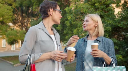 milestone : Cheerful female friends beautiful women are walking in green park chatting laughing holding coffee and shopping bags. Consumerism and recreation concept. Stock Footage