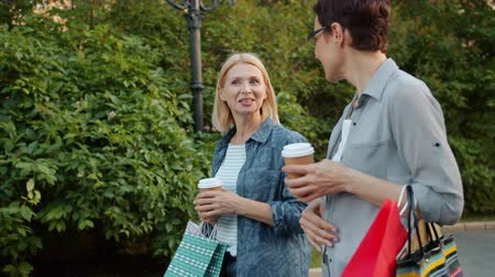 milestone : Slow motion of good-looking ladies friends walking in park with shopping paper bags talking smiling holding to go coffee on warm summer day. People and lifestyle concept.