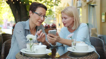 milestone : Beautiful mature women friends are using smartphone talking laughing looking at screen sitting in street cafe at table. Modern technology and friendship concept. Stock Footage
