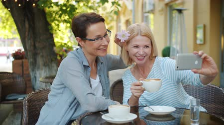 photograph : Happy friends beautiful mature women are taking selfie in street cafe using smartphone camera decorating hair with flower smiling posing holding coffee cup.