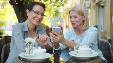 milestone : Excited mature women are using smartphone talking laughing sitting in open air cafe in city street. Modern technology, happiness and urban lifestyle concept.