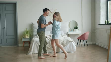 pense bête : Cheerful girl and guy happy couple are dancing in bedroom at home on floor having fun in modern apartment. Joyful people, lifestyle and leisure time concept.