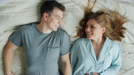 casal : Slow motion of young loving couple husband and wife falling on bed smiling relaxing enjoying romantic relationship at home. People and lifestyle concept. Stock Footage