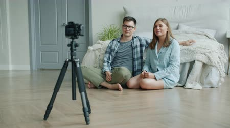 пижама : Attractive husband and wife bloggers are recording video for vlog, waving hands and gesturing, talking and laughing, they are using camera on tripod and sitting on bedroom floor.