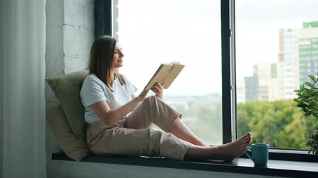 читатель : Beautiful girl student is reading interesting book turning pages sitting on window-sill at home in modern apartment. Literature, youth culture and interiors concept. Стоковые видеозаписи