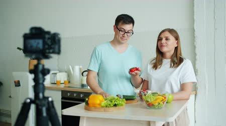 штатив : Happy family young husband and wife are recording video about organic vegetables holding tomatoes talking waving hand at home using camera on tripod.