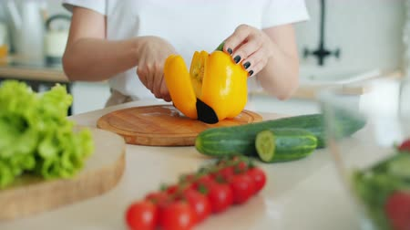 полезный : Close-up of girls hand cutting beautiful fresh pepper on wooden board using knife cooking salad alone at home. People, diet and nutrition concept.