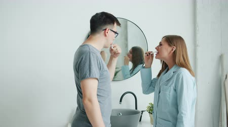 escova de dentes : Attractive man and woman in pajamas happy couple are brushing teeth talking smiling in modern apartment. Casual hygiene, relationship and people concept.