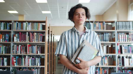 dedicado : Portrait of serious teenage boy walking in school library with books alone looking around on shelves. Education, campus interior and students concept. Vídeos