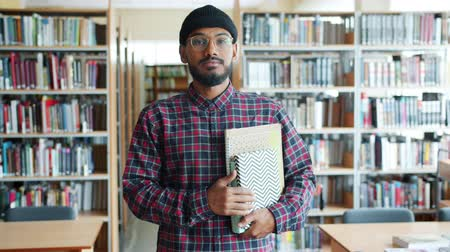 irodalom : Portrait of serious African American guy student holding books in university library looking at camera alone. Reading, knowledge and education concept. Stock mozgókép