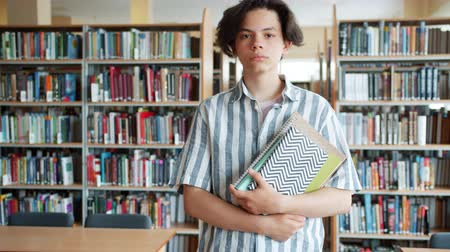 čtenář : Slow motion portrait of good-looking teenage student standing in library with books and looking at camera with serious face. People and knowledge concept. Dostupné videozáznamy