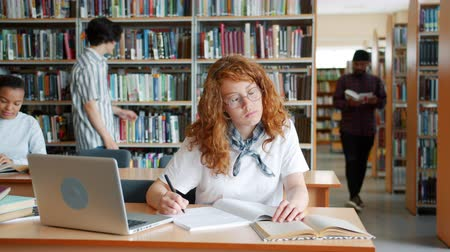 alfabetização : Female student is doing research in library reading book and writing while people girl and guys are studying in background. Lifestyle and academic education concept.