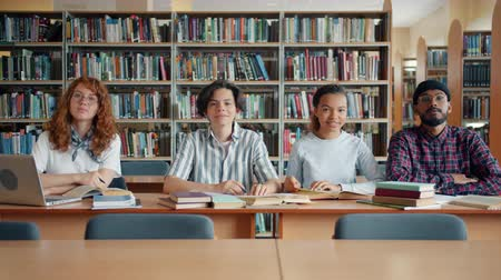 старшей школе : Portrait of cheerful young people students sitting in college library together smiling looking at camera. Education, happy people and lifestyle concept. Стоковые видеозаписи