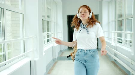 dospívání : Cheerful teenager in headphones enjoying music dancing in school hall having fun wearing casual clothing and holding backpack. People and lifestyle concept.