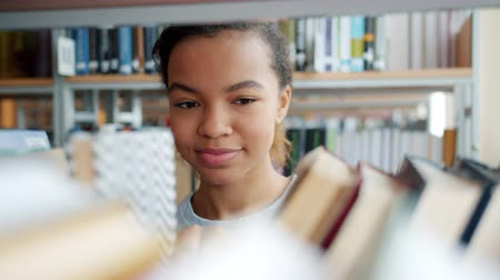 knihkupectví : Portrait of cheerful African American teenager choosing books in school library touching textbooks smiling. Education, people and youth culture concept.