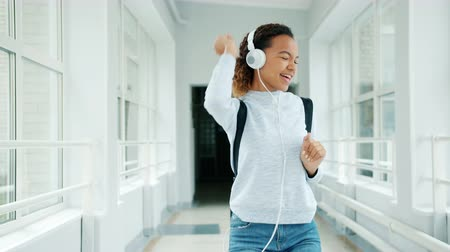 acadêmico : Joyful girl in headphones having fun in university hall singing dancing walking among students with backpacks. Modern lifestyle, happiness and devices concept.