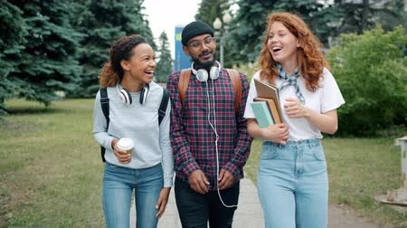 mates : Slow motion of cheerful men and women students walking outdoors on campus with books and coffee talking laughing enjoying freedom after college classes.