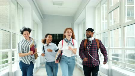 amigos : Happy friends girls and guys are running in school hallway doing high-five laughing jumping holding books. People, lifestyle and positive emotions concept.