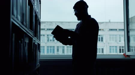 alfabetização : Silhouette of male student looking through books in university library reading standing near bookshelf alone. Culture, adolescence and lifestyle concept. Vídeos