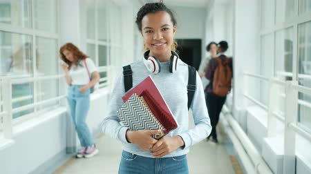 mais alto : Joyful mixed race teenager girl is holding books standing in college hallway smiling looking at camera, multi-ethnic group of students is visible in background.
