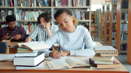 diligencia : Tired African American girl diligent student is studying in college library writing reading books feeling exhausted. People, emotions and education concept.