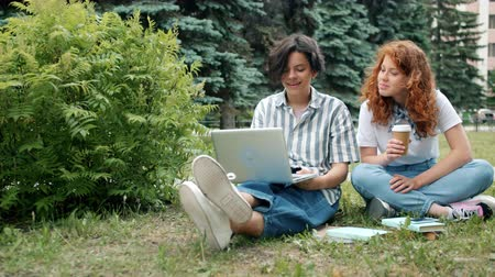 mates : Couple of students are studying outdoors using laptop reading books talking working at project together, girl is drinking to go coffee. Devices and education concept.