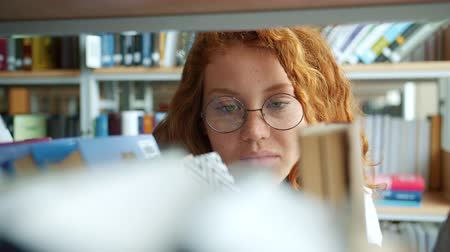 knihkupectví : Young lady with curly red hair is choosing book in bookstore taking volume from shelf smiling reading indoors. Education, literature and students concept.