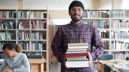 literatuur : Slow motion of handsome African American guy student walking in library with books smiling looking at camera. Education, literature and people concept.