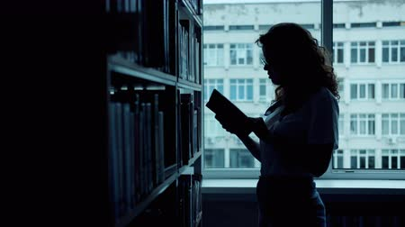 читатель : Silhouette of smart woman choosing interesting book in college library reading holding in hands standing alone in dark room. Education and lifestyle concept.