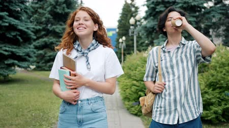 старшей школе : Couple of teenagers girl and guy are walking outdoors talking holding books drinking take out coffee having fun. Lifestyle, people and communication concept. Стоковые видеозаписи