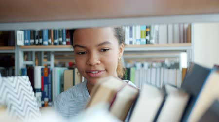 livros : Portrait of attractive mixed race lady choosing books on shelf in bookshop holding reading smiling. Smart youth, education and modern lifestyle concept.