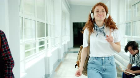 dospívání : Pretty redhead student in headphones is dancing in high school lobby having fun with music enjoying happy day and leisure time. People and entertainment concept. Dostupné videozáznamy