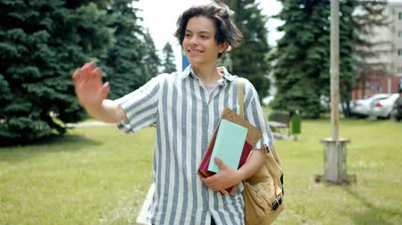 adolescência : Cheerful guy student is walking outdoors in park waving hand greeting friends holding books smiling looking around. Happy people and lifestyle concept.