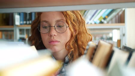 livraria : Pretty redhead girl in glasses is choosing book in bookshop reading with serious face looking through tome. Lifestyle, smart students and library concept.