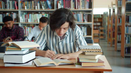 diligence : Slow motion of tired teenage boy studying in college library reading book at desk with exhausted face. Hard-working students, education and emotions concept.