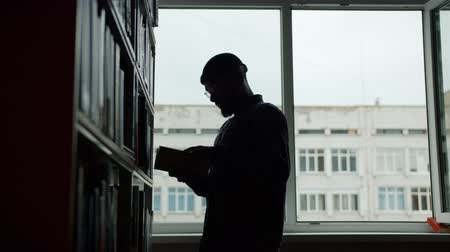 alfabetização : Bearded African American man is taking book from shelf in college library reading standing near bookshelf alone in dark room. People and education concept. Vídeos