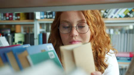 livraria : Female student beautiful redhead girl is choosing book in university library reading smiling alone indoors. Lifestyle, hobby and modern literature concept.