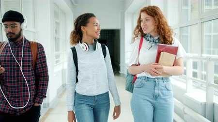 mates : Slow motion of happy young ladies walking in college hall with backpacks and books doing high-five chatting smiling. Communication and education concept.