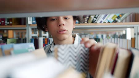 knihkupectví : Portrait of cheerful teenager choosing books in high school library smiling reading textbook alone indoors. Literature, youth culture and lifestyle concept.